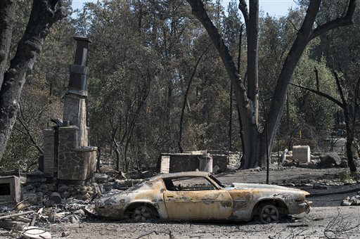 Scorched trees and burned vehicles and the remains of homes cover the landscape Thursday Sept. 17, 2015, in Anderson Springs, Calif. (Paul Kitagaki Jr./The Sacramento Bee via AP)