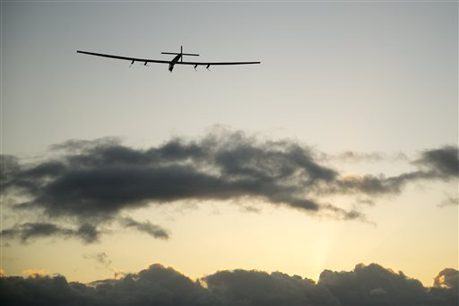 The Solar Impulse 2 solar plane flies into the sunrise out of Kalaeloa Airport on Thursday in Kapolei, Hawaii. (AP Photo/Marco Garcia)