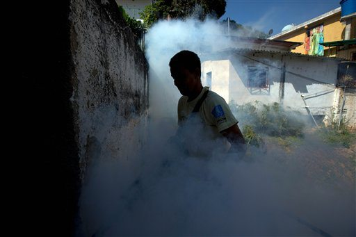 A Sucre municipality worker fumigates for Aedes aegypti mosquitoes that transmit the Zika virus in the Petare neighborhood of Caracas, Venezuela, Monday. (AP Photo/Fernando Llano)
