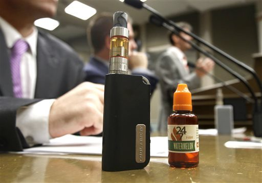 An E-Cigarette and E-Liquid are displayed during an Assembly committee hearing on a measure to regulate E-Cigarettes at the Capitol Wednesday, July 8, 2015, in Sacramento,Calif. (Rich Pedroncelli/AP Photo)
