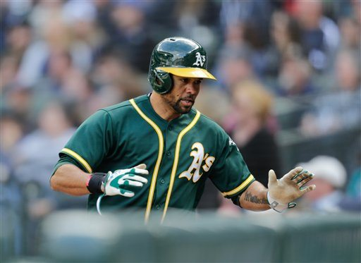 Oakland Athletics' Coco Crisp heads to the dugout after hitting a solo home run on a pitch from Seattle Mariners' Nick Vincent during the 10th inning Sunday in Seattle. (AP Photo/John Froschauer)