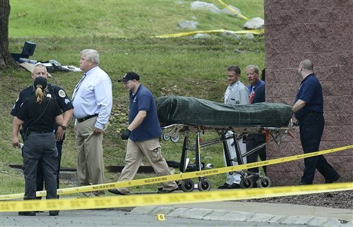 The body of the suspect is removed from a movie theater following a shooting Wednesday. (AP Photo/Mark Zaleski)