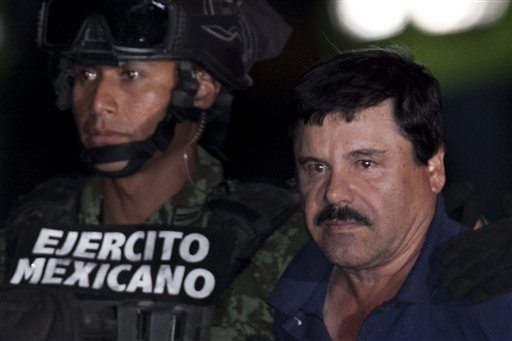 "Mexican drug lord Joaquin ""El Chapo"" Guzman, right, is escorted by soldiers and marines to a waiting helicopter, at a federal hangar in Mexico City, Friday. (AP Photo/Marco Ugarte)"