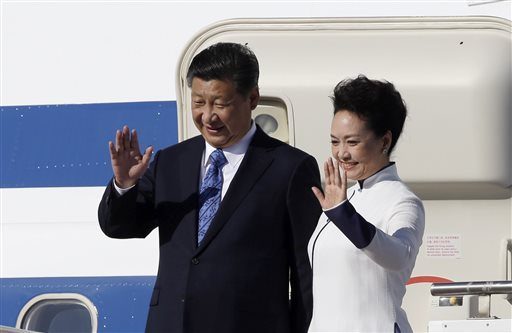 Chinese President Xi Jinping, left, and his wife Peng Liyuan wave upon arrival Tuesday at Boeing Field in Everett, Wash. (AP Photo/Elaine Thompson)
