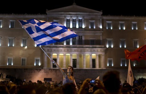 A supporter of the No vote waves a Greek flag in front of the parliament after the results of the referendum at Syntagma square in Athens on Sunday. (AP Photo/Emilio Morenatti)