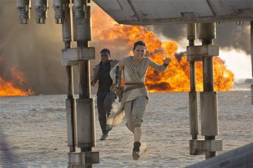 """This photo provided by Disney/Lucasfilm shows Daisy Ridley, right, as Rey, and John Boyega as Finn, in a scene from the film, """"Star Wars: The Force Awakens,"""" directed by J.J. Abrams. (David James/Disney/Lucasfilm via AP)"""