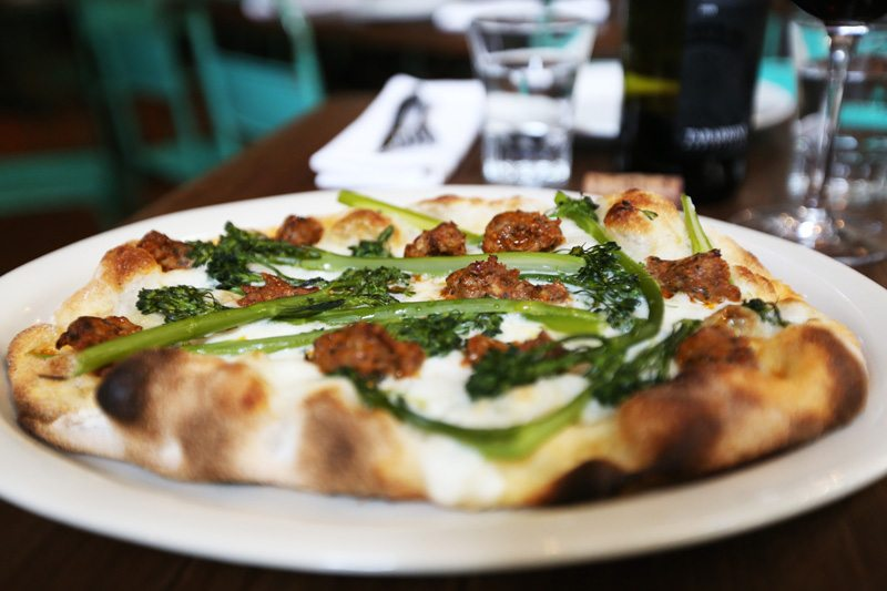 Pinsa – a Roman dish considered a precursor to pizza – is served at Montesacro. The   luscious Maranella, pictured, has spicy sausage, broccolini and burrata. (Natasha Dangond/Special to S.F. Examiner)