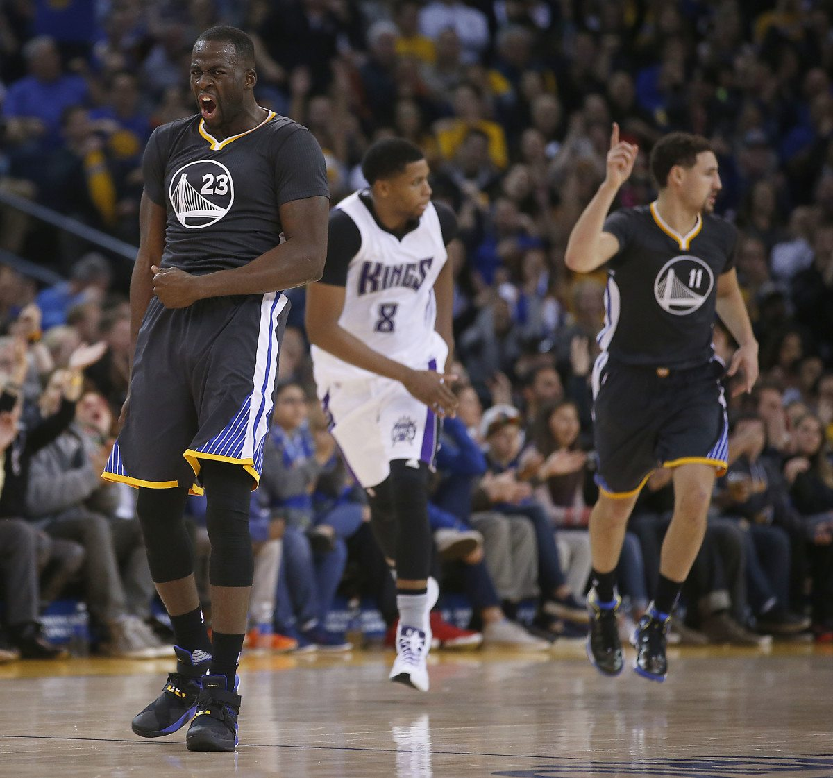 Golden State Warriors forward Draymond Green (23) reacts after guard Klay Thompson, right, hit a three-point shot against Sacramento Kings forward Rudy Gay, center, during the first half of an NBA basketball game Saturday, Nov. 28, 2015, in Oakland, Calif. (Tony Avelar/AP)