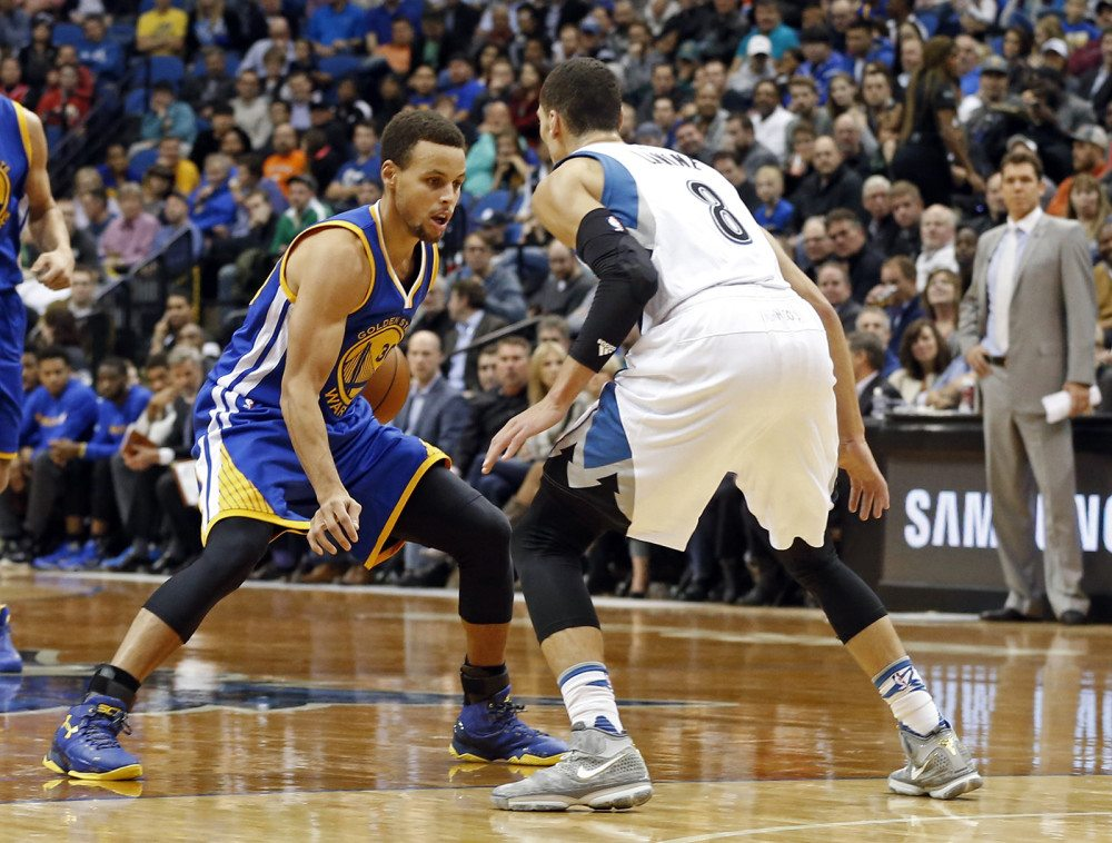 Stephen Curry, left, looks to move past the Timberwolves' Zach LaVine during the second half of an NBA basketball game, Thursday, Nov. 12, 2015, in Minneapolis. The Warriors won  129-116. (Jim Mone/AP)