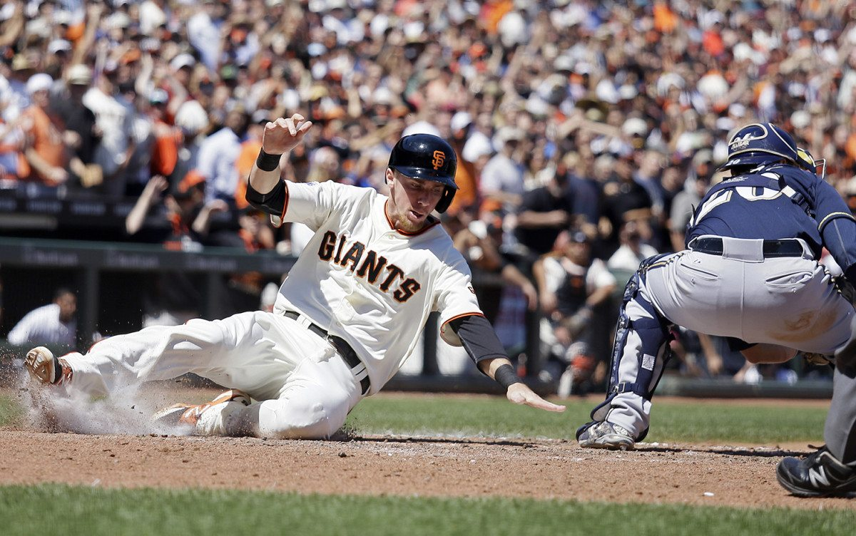 Giants third baseman Matt Duffy, left, slides into home plate and scores the Giants' first run against the Milwaukee Brewers on Wednesday afternoon. (Eric Risberg/AP)
