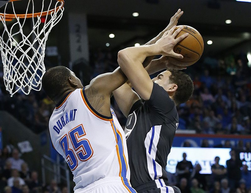 Golden State Warriors guard Klay Thompson, right, is fouled as he shoots by Oklahoma City Thunder forward Kevin Durant (35) during the second quarter of an NBA basketball game in Oklahoma City, Saturday, Feb. 27, 2016. (Sue Ogrocki/AP)
