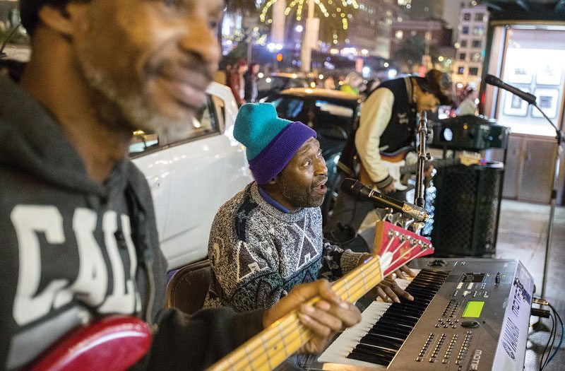 Street performers Lawrence Wilburn, left, and Jack Jefferson, center, jam with other musicians on the corner of Geary and Powell streets in San Francisco's Union Square on Tuesday. (Jessica Christian/S.F. Examiner)