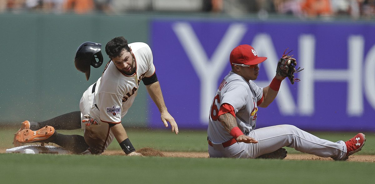 San Francisco Giants' Brandon Belt, left, loses his helmet after being tagged out at second base by St. Louis Cardinals' Kolten Wong, right, on a steal-attempt in the fourth inning on Saturday. (Ben Margot/AP)