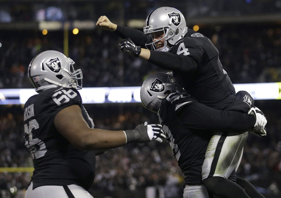 Oakland Raiders quarterback Derek Carr, top, celebrates with guard Gabe Jackson, left, and offensive guard Jon Feliciano after the Raiders scored against the San Diego Chargers during the second half of an NFL football game in Oakland, Calif., Thursday, Dec. 24, 2015. (Marcio Jose Sanchez/AP)
