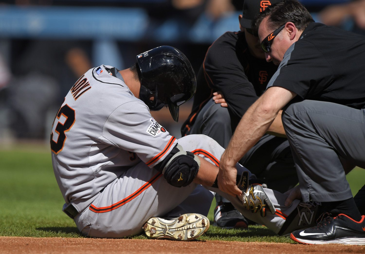 Giants' Nori Aoki, left, is checked by trainers after he was hit by a pitch on Saturday against the Los Angeles Dodgers. (AP Photo/Mark J. Terrill)