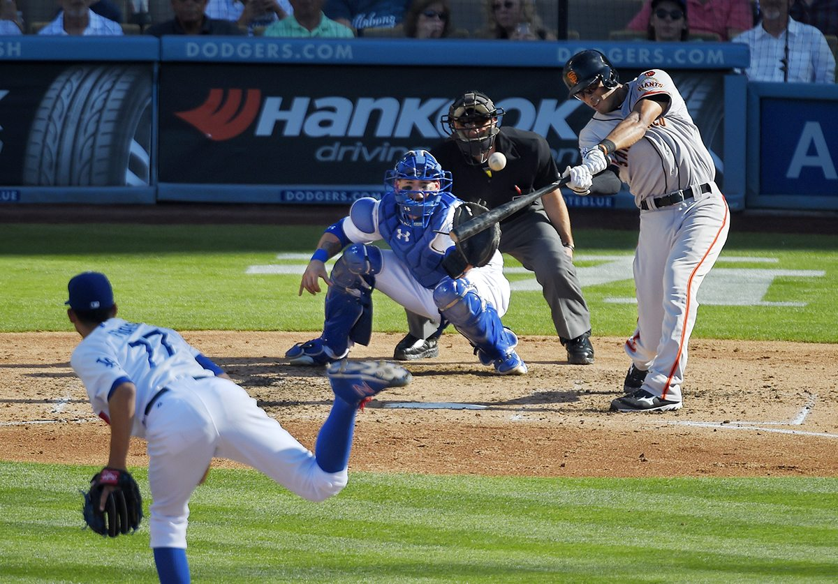 San Francisco Giants' Justin Maxwell, right, hits a two-run home run as Los Angeles Dodgers starting pitcher Carlos Frias, left, catcher Yasmani Grandal, second from left, and home plate umpire Chris Guccione watch during the fifth inning of a baseball game, Saturday, June 20, 2015, in Los Angeles. (AP Photo/Mark J. Terrill)