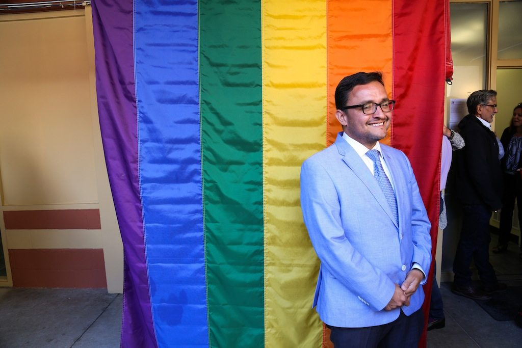 Supervisor Dave Campos stands in front of a Pride Flag at  the grand opening of the new LGBT homeless shelter, Jazzie's Place. 1050 South Van Ness Ave., San Francisco. Wednesday June 17, 2015.