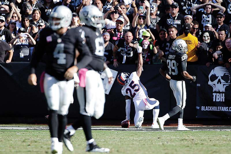 Raiders quarterback Derek Carr is left to walk away as Denver's Chris Harris Jr. celebrates his 74-yard interception return for a touchdown Sunday. (AP Photo/Marcio Jose Sanchez)
