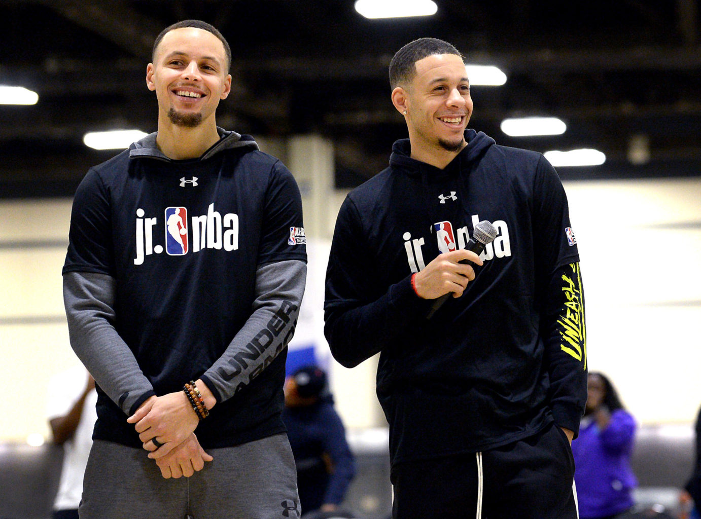 NBA stars Golden State Warriors Stephen Curry, left, smiles as his brother, Seth Curry of the Portland Trail Blazers, right, addresses students during the Fourth Annual Jr. NBA Day at the Charlotte Convention Center on Friday, Feb. 15, 2019, in Charlotte, N.C. (Jeff Siner/Charlotte Observer/TNS)