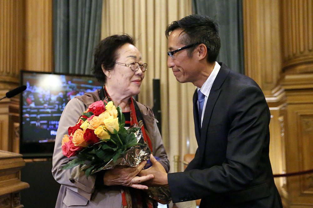 "Yong Soo Lee, left, a ""comfort woman"" survivor, receives a commendation from Supervisor Eric Mar at the Board of Supervisors meeting on Tuesday.(Mike Koozmin/S.F. Examiner)"