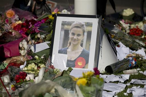 A photograph of Jo Cox, the 41-year-old Member of Parliament fatally shot last week in northern England, stands amongst tributes laid in her memory in Parliament Square, London, after a service of prayer and remembrance to commemorate her, Monday. (AP Photo/Matt Dunham)