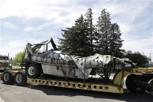 (AP Photo/Jeff Chiu)The demolished remains of a FedEx truck is towed into a CalTrans maintenance station in Willows