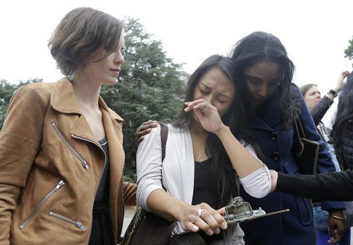 University of California graduate student Kathleen Gutierrez, center, is comforted by graduate student Erin Bennett, left, and Tyann Sorrell before all spoke at a news conference outside of Dwinelle Hall on the campus in Berkeley on Monday. (AP Photo/Jeff Chiu)