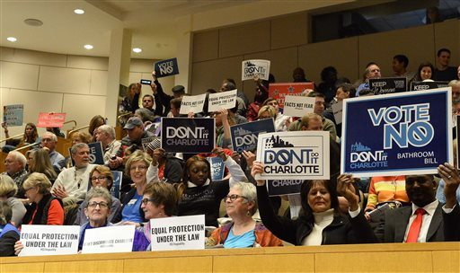 In this photo taken on Monday, members of the audience hold up signs before the start of a City Council meeting's vote on the nondiscrimination ordinance, in Charlotte, N.C. (Robert Lahser /The Charlotte Observer via AP)