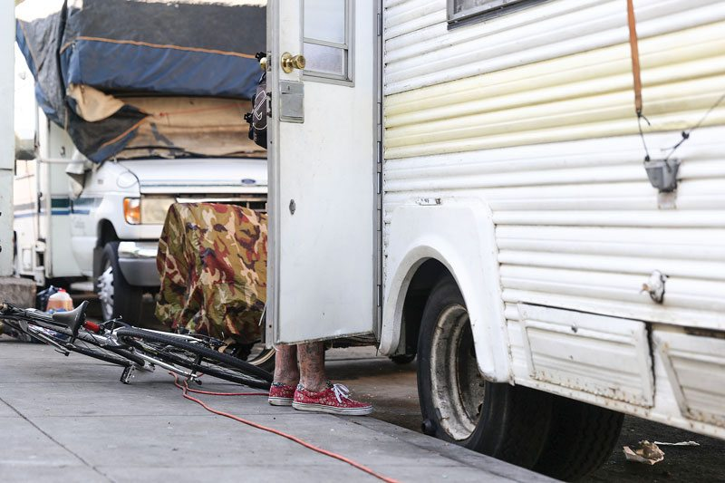 A man stands by the door of a mobile home seen on Division Street on Nov. 2. (Aleah Fajardo/Special to S.F. Examiner)