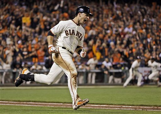 David J. Phillip/APThe Giants' Buster Posey is pumped after delivering an RBI single during the sixth inning of Wednesday's Game 4 of the NL Championship Series.