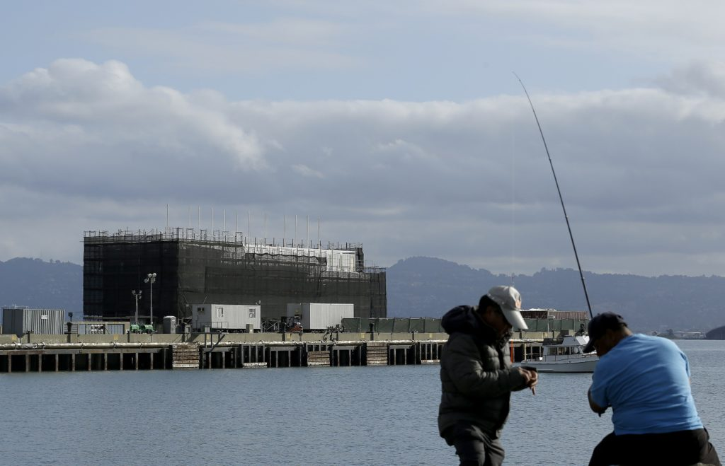 AP Photo/Jeff ChiuTwo men fish in the water in front of a barge on Treasure Island in San Francisco
