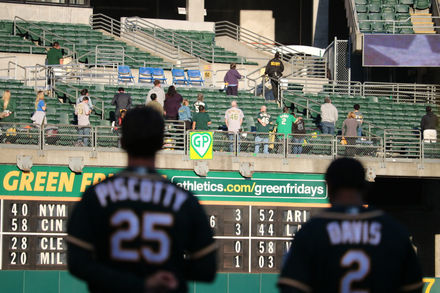 Stephen Piscotty stands for the national anthem on May 8 as a sign honoring his mother is held in the right field stands. (Courtesy: Oakland Athletics)