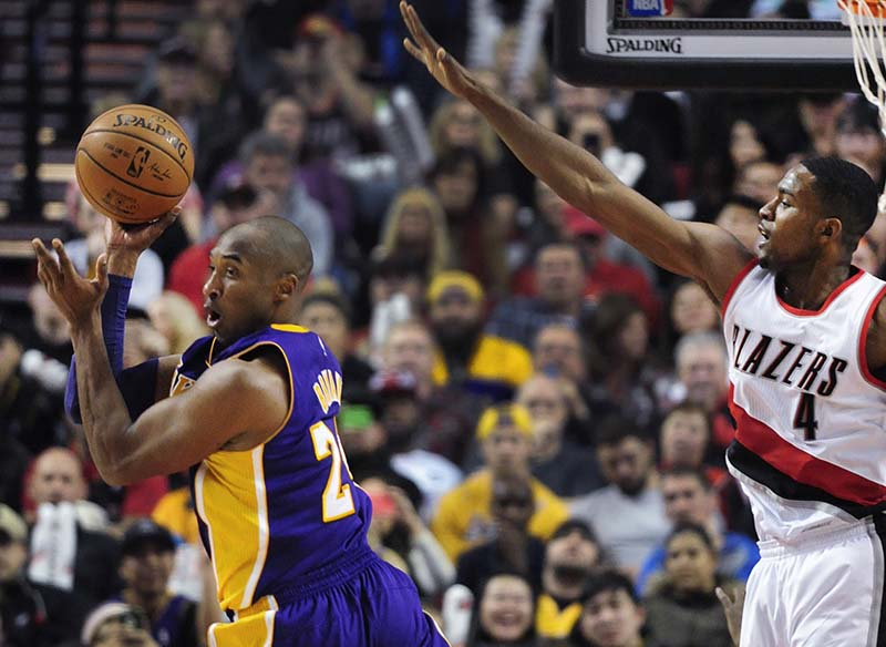 Los Angeles Lakers forward Kobe Bryant (24) looks to pass the ball as Portland Trail Blazers forward Maurice Harkless defends during the second half of an NBA basketball game Saturday. (AP Photo/Steve Dykes)