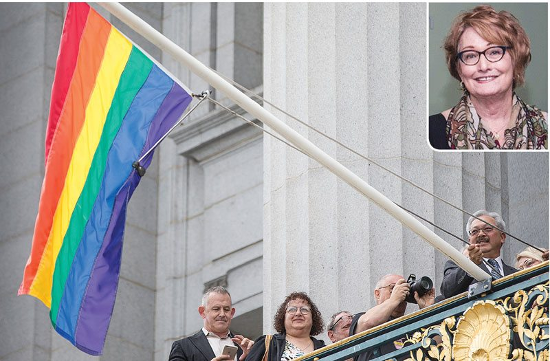 Mayor Ed Lee raises the LGBT Pride flag from his balcony at San Francisco City Hall on Friday. (Jessica Christian/S.F. Examiner)