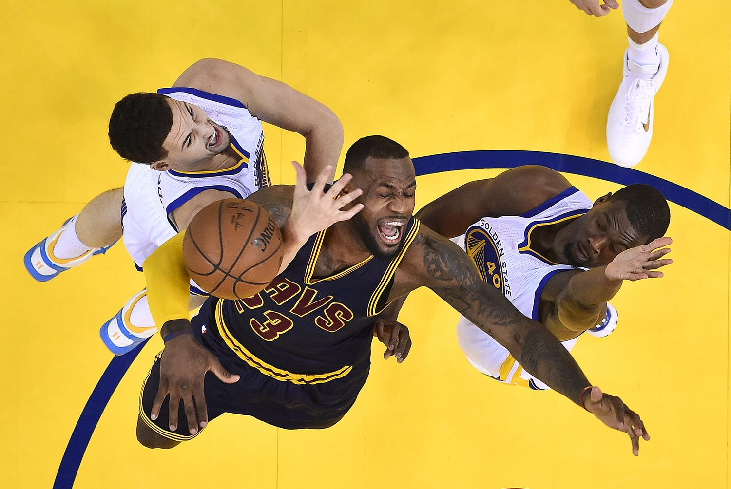 Cleveland Cavaliers forward LeBron James, center, loses the ball between Golden State Warriors guard Klay Thompson, left, and forward Harrison Barnes during the first half of Game 1 of basketball's NBA Finals in Oakland, Calif., Thursday, June 4, 2015. The Warriors won 108-100 in overtime. (John G. Mabanglo/EPA Pool via AP)