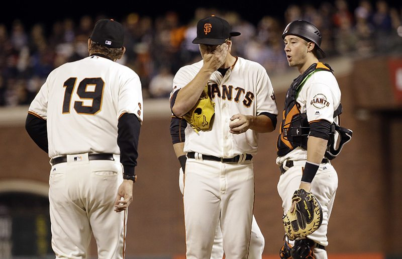 Matt Cain, center, gets a visit to the mound from pitching coach Dave Righetti (19) after Cain gave up an RBI triple to Arizona Diamondbacks' Jake Lamb during the fifth inning of Tuesday's game. (Marcio Jose Sanchez/AP)