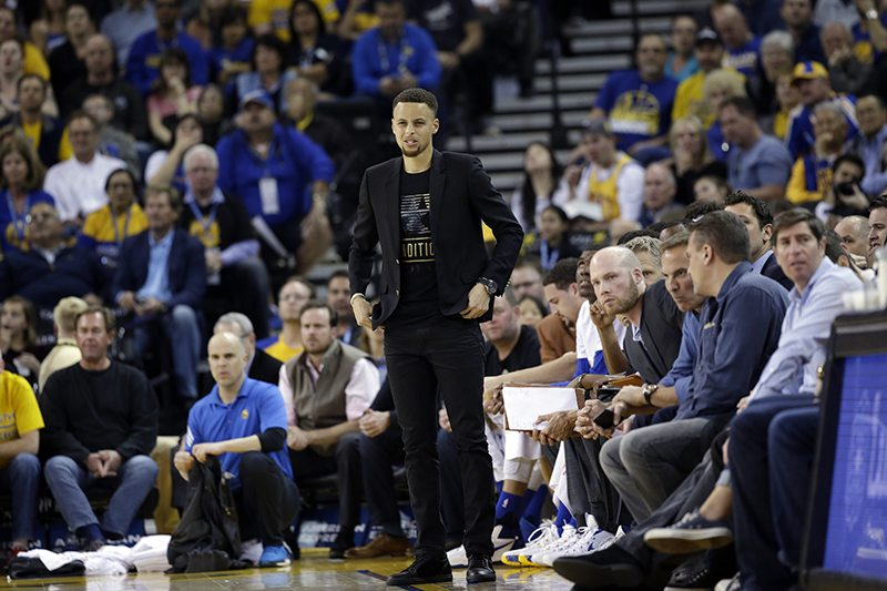 Golden State Warriors' Stephen Curry watches from the bench during the first half of an NBA basketball game against the Atlanta Hawks Tuesday, March 1, 2016, in Oakland, Calif. (Marcio Jose Sanchez/AP)