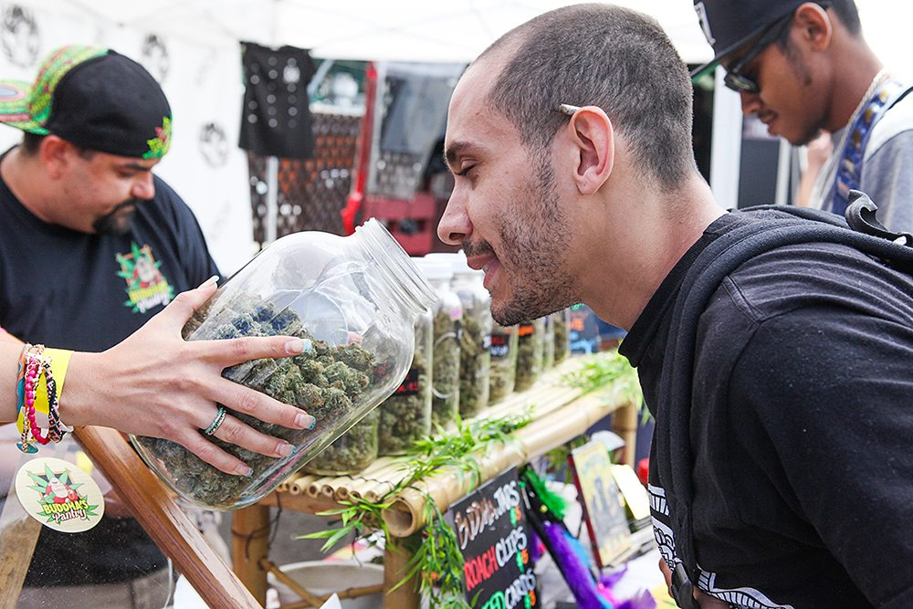 "A customer takes a whiff of Buddha's Pantry's marijuana from Brandy Turnbull (left) at the ""Get Baked Sale"" held at  SOMAStreat Food Park on 11th Street, Saturday, June 13, 2015 in San Francisco. The event included food trucks and various booths promoting their companies. There were the typical edibles like cookies and brownies as well as the more innovative products like marijuana infused olive oil. Over 25 local businesses hosted the event. Photos by Gabrielle Lurie/Special to the S.F. Examiner."