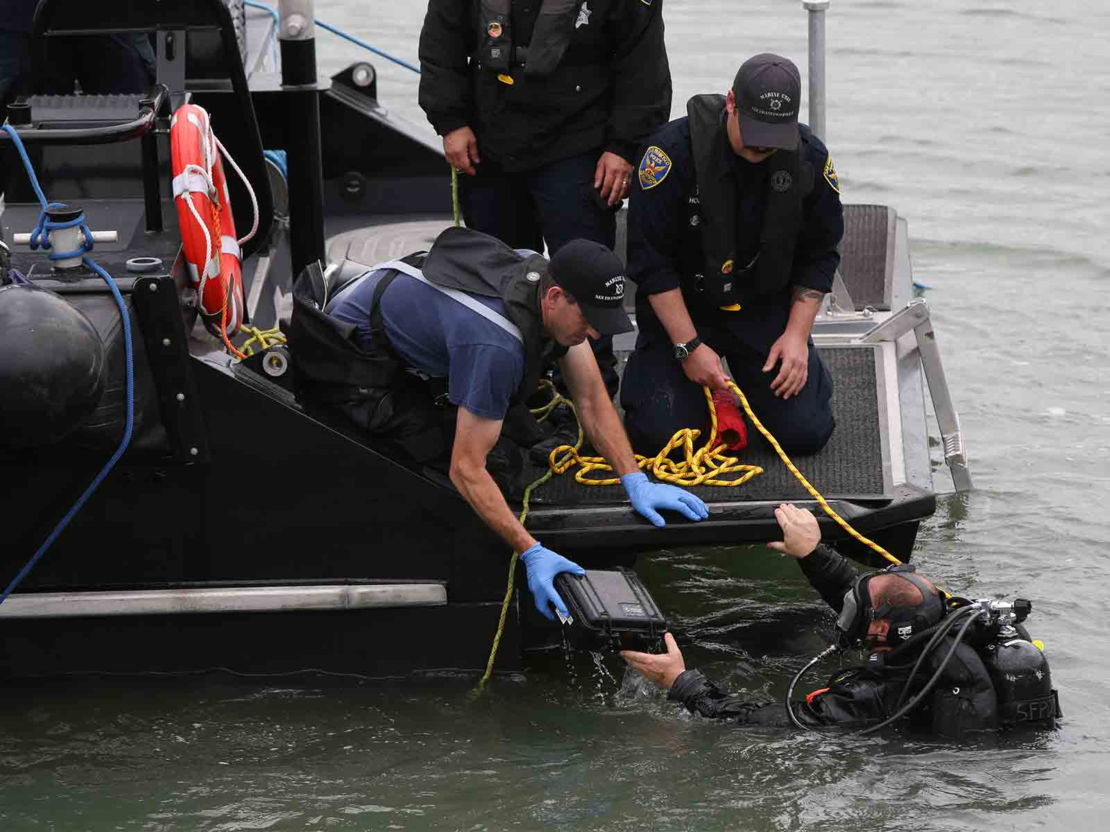 San Francisco police divers search the waters south of Pier 14 and retrieve an object they placed into a plastic box on July 2, 2015, one day after the fatal shooting of Kate Steinle. (Mike Koozmin/2015 S.F. Examiner)