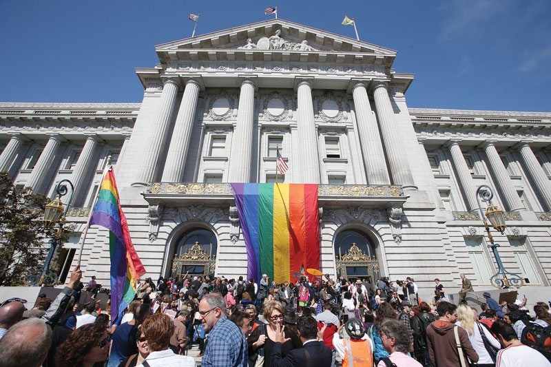 People rejoice at the foot of a massive rainbow flag hung from the balcony of San Francisco City Hall on Friday to celebrate the Supreme Court's historic ruling that the 14th Amendment guarantees same-sex couples the right to marry. (Mike Koozmin/S.F. Examiner)