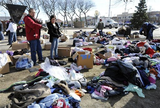 AP Photo/Kathy KmonicekTwo people look over piles of clothing in front of Long Beach city hall donated for victims of Superstorm Sandy on Tuesday