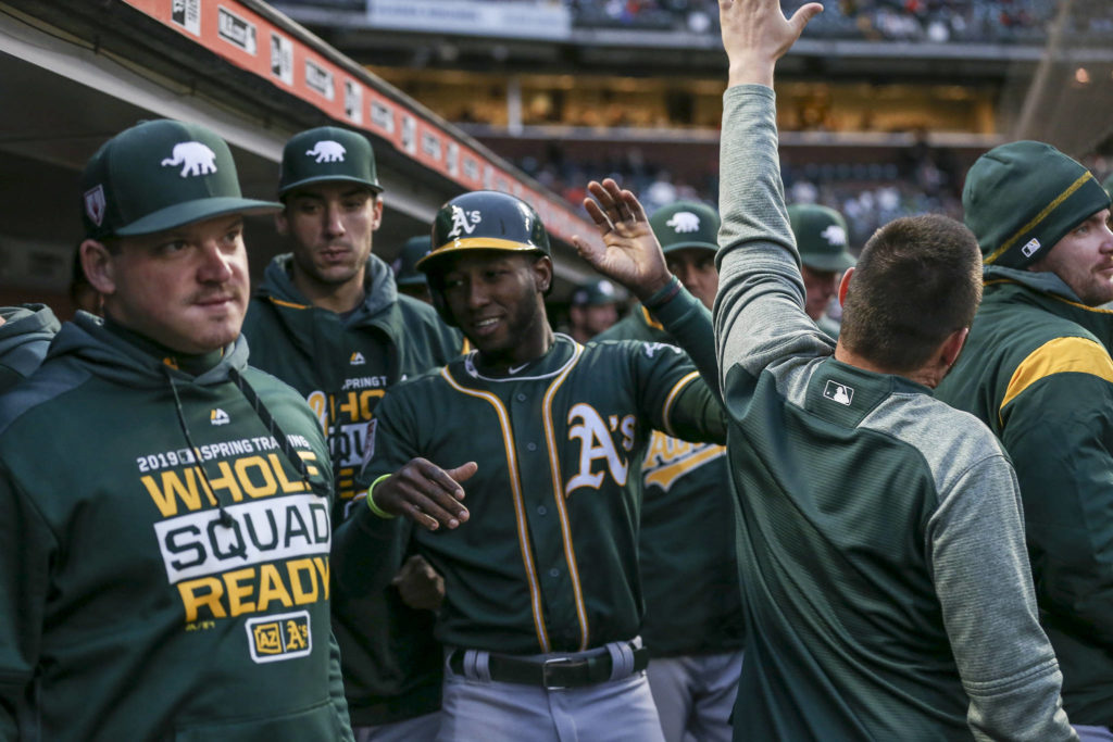 Oakland A's teammates congratulate Jurickson Profar (23) after scoring on a double from teammate Mark Canha (20) in the 2nd inning against the San Francisco Giants at Oracle Park on March 26, 2019 in San Francisco, California. (Chris Victorio | Special to S.F. Examiner)