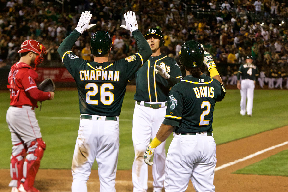Oakland Athletics' Matt Chapman and Khris Davis congratulate Stephen Piscotty after hitting a three-run homer against the Los Angeles Angels at Oakland Coliseum on Wednesday, Sept. 19, 2018. (Kevin N. Hume/S.F. Examiner)