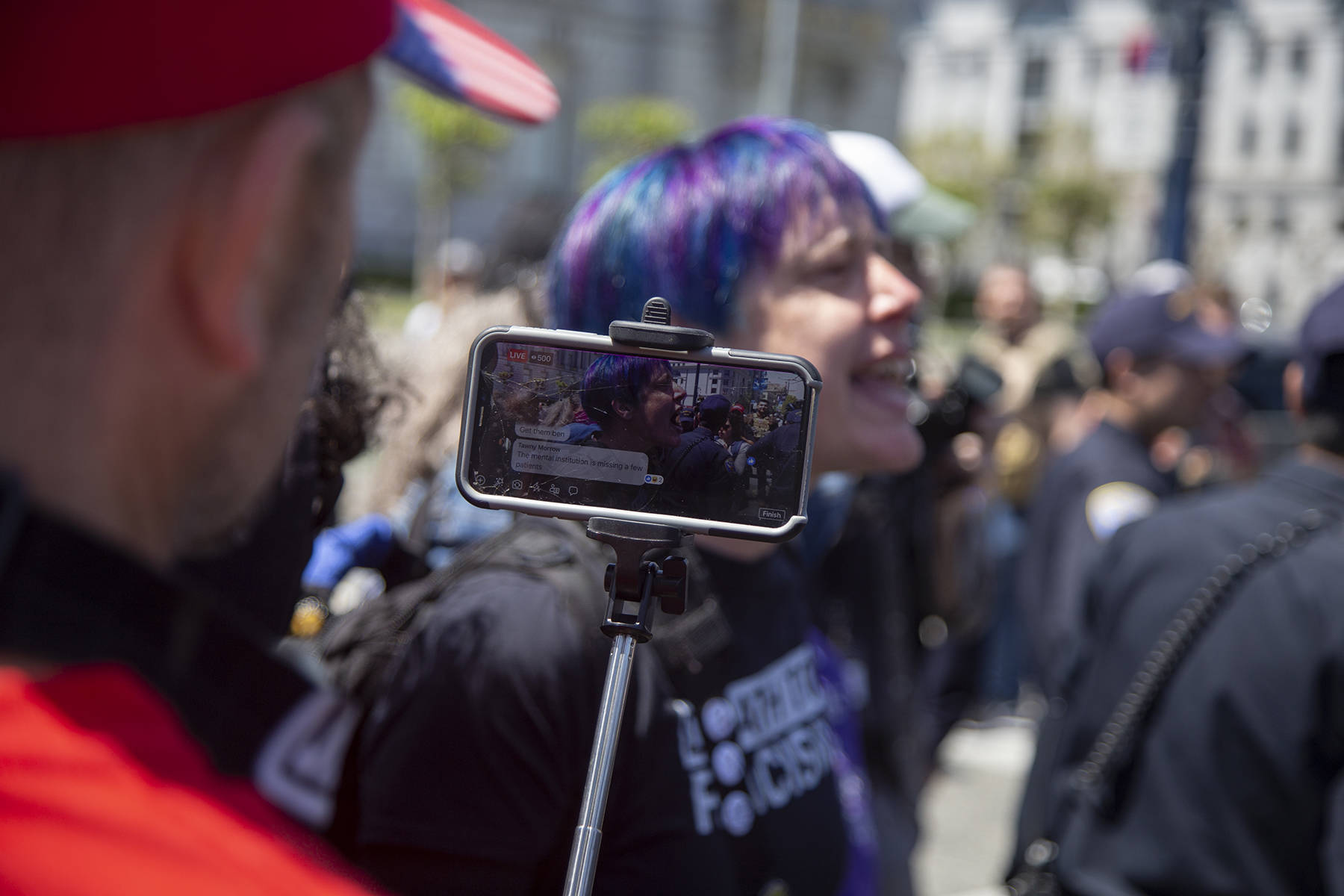 """A man wearing MAGA gear records counter protester Banasidhe on Facebook Live during the """"Demand Free Speech"""" rally on City Hall steps on Friday, May 3, 2019. (Ellie Doyen/Special to S.F. Examiner)"""