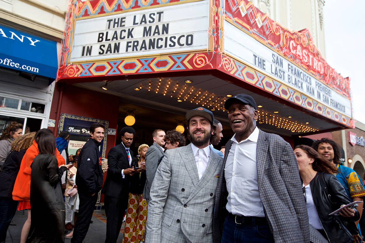 """Writer-director Joe Talbot and actor Danny Glover smile for photos under the marquee at the San Francisco premiere of """"The Last Black Man in San Francisco"""" at the Castro Theater on Wednesday, May 29, 2019. (Kevin N. Hume/S.F. Examiner)"""