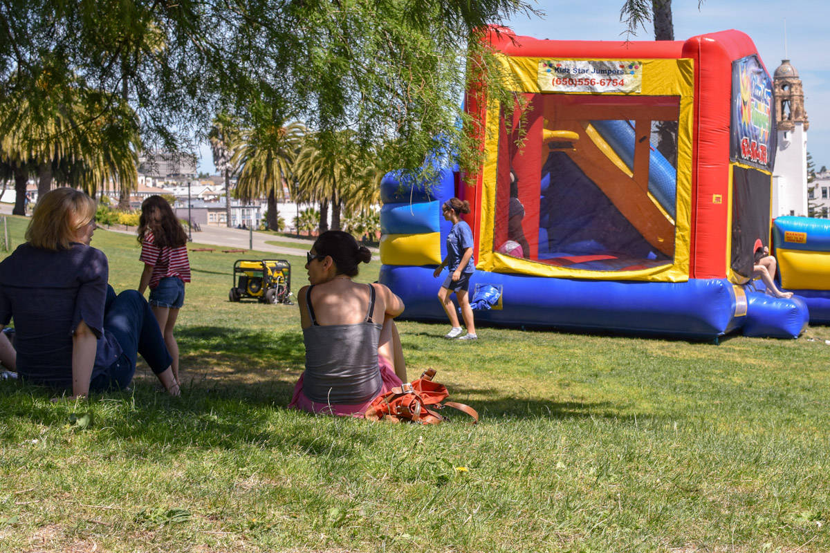 Mothers sit and chat in the shade as children play and use a bounce house in the sun at Dolores Park, San Francisco on Monday, June 10, 2019. (Lola Chase/ Special to SF Examiner)