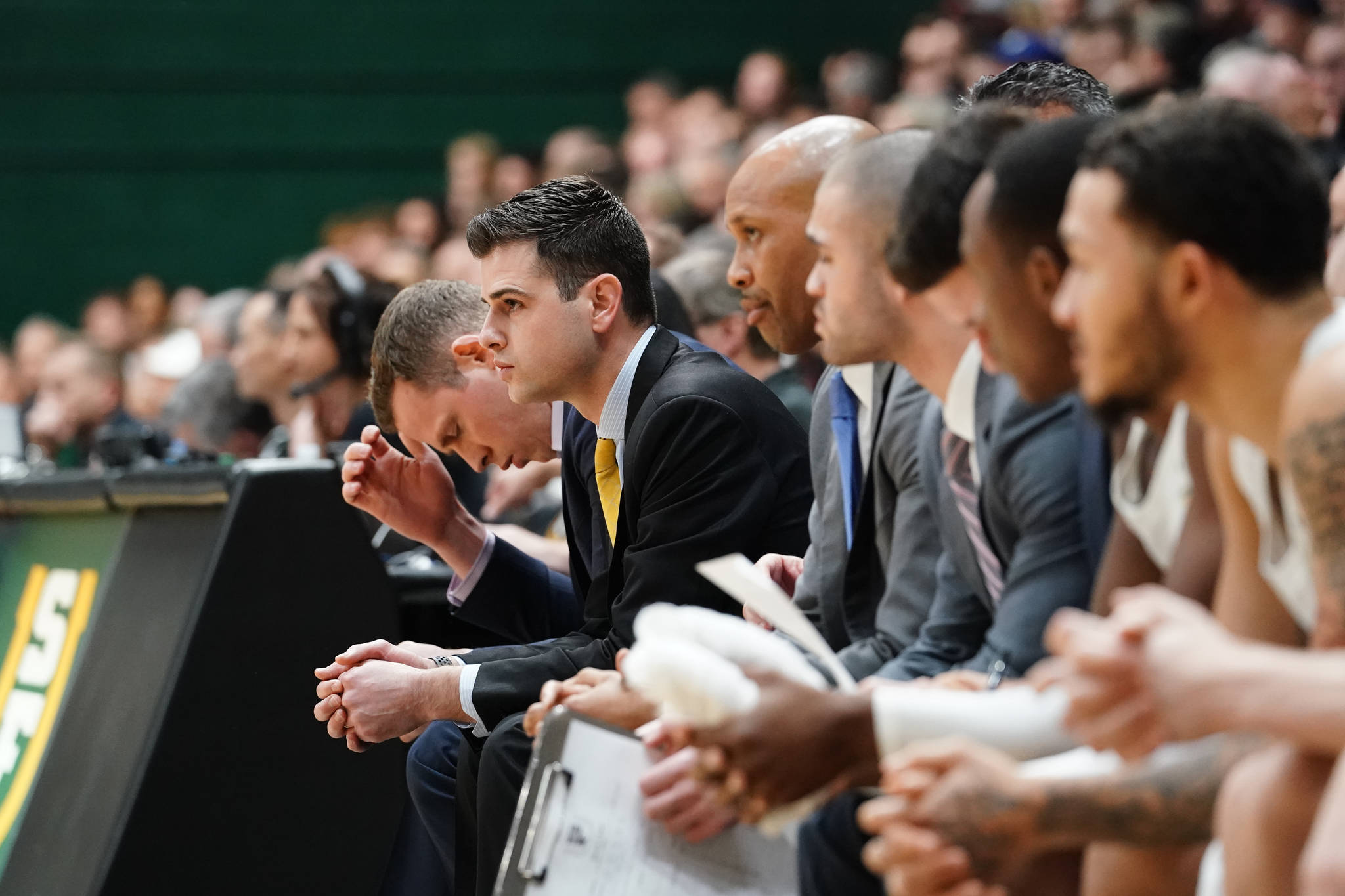 Todd Golden (center) sits on the bench during the University of San Francisco Dons' basketball game on jan. 12, 2019 against No. 5 Gonzaga at War Memorial Gym in San Francisco, Calif. (Courtesy / Chris M. Leung / USF Dons Athletics)