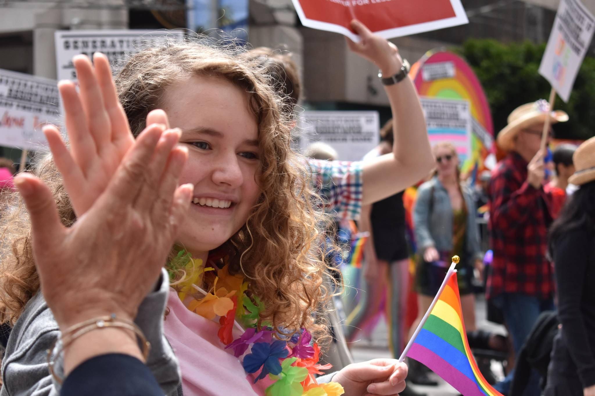 A young girl marching in the SF Pride Parade high-fives a spectator. (Lola Chase / Special to the S.F. Examiner)