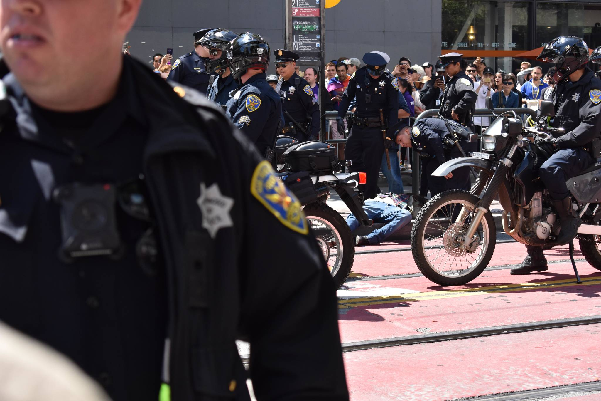 Police detain a protester and hold him on the pavement during a protest on Sunday, June 30, 2019. (Lola Chase/ Special to S.F. Examiner)