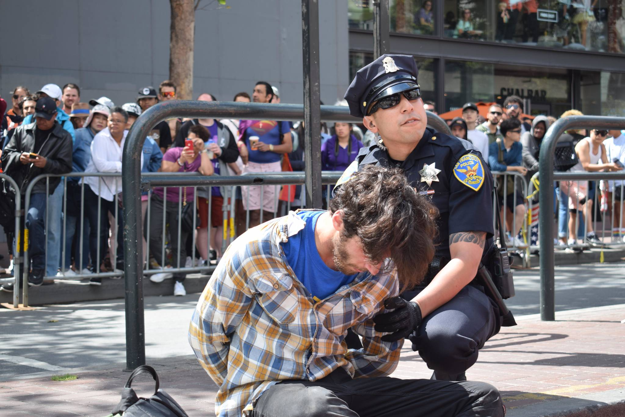 San Francisco Police hold a second handcuffed protester at the Powell Street BART station. (Théophile Larcher/ Special to S.F. Examiner)